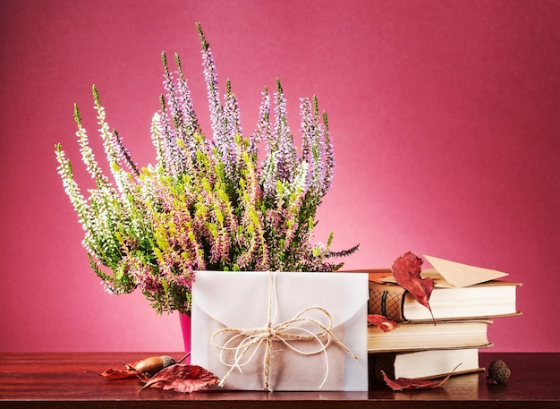 Herfst verrassing. stilleven met gesloten witte envelop, heidebloemen, droge bladeren en boeken