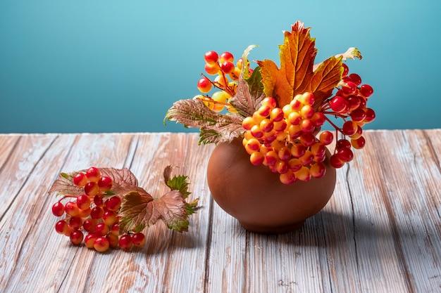 Herfst viburnum in klei pot op hout