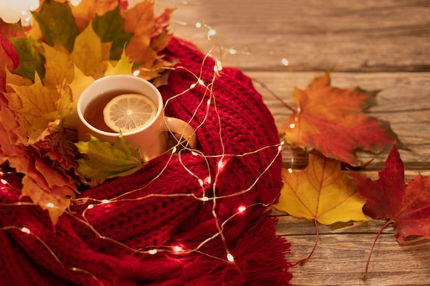 Herfst warme compositie in rode tinten op een houten ondergrond met een kopje thee, garland