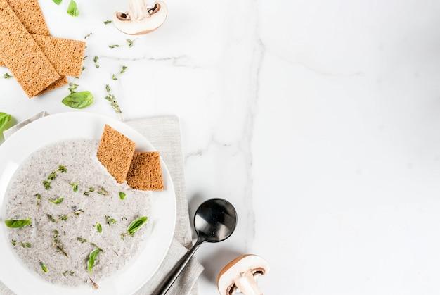 Herfst warme gerechten. veganistische soepen. champignonroomsoep met bruin gefrituurde champignons en kruiden, tijm. op een witte marmeren tafel. copyspace bovenaanzicht