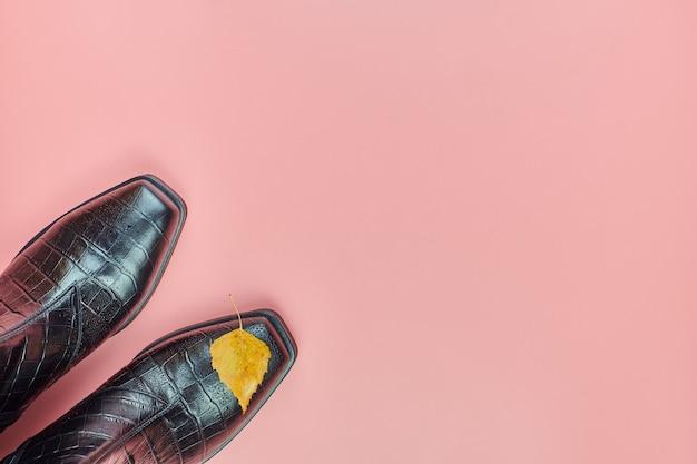 Herfst waterdichte vrouw schoenen met regendruppels, kopie ruimte. schoen zorg concept. regendichte laarzen met herfstblad als symbool regenachtig weer.