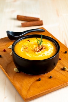 Herfst winter food-concept pompoen of butternut soep in zwarte kom op houten achtergrond