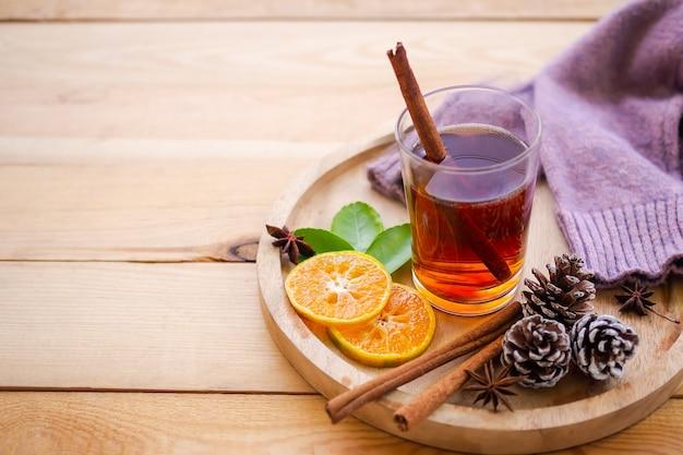 Herfst, winter hete thee drinken concept. thee in glas met kruiden en steranijskruidvruchten, schilferige sinaasappel, dennenappels, trui op houten plaat met houten achtergrond.