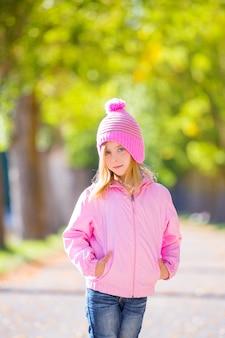 Herfst winter jongen meisje blond met jeans en roze sneeuw dop