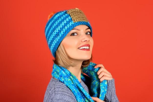 Herfst/winter mode, stijl mensen concept - vrolijk meisje in modieuze gebreide muts, sjaal, grijze trui. aantrekkelijk sexy meisje met perfecte huid en make-up. kopieer ruimte voor het adverteren van kledingwinkel.