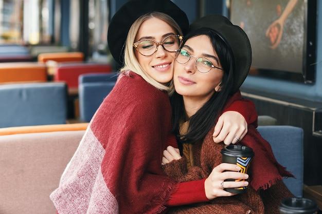 Herfst winter portret van twee jonge vrouwen in een terras, knuffelen, koffie drinken om te gaan.