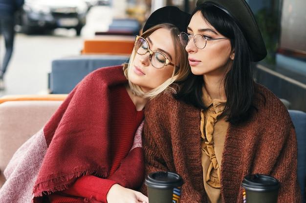 Herfst winter portret van twee modieuze vrouwen in een terras, koffie drinken om te gaan, poseren.