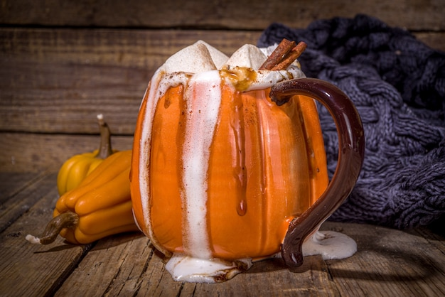 Herfst, winterdrankje voor kerstmis, thanksgiving, halloween. grappige kop pittige pompoen latte, warme chocolademelk, met slagroom, marshmallow, kruiden met boek, warme plaid en decoratie