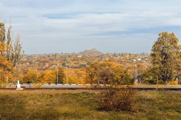 Herfst zonnig landschap. uitzicht op een herfst stad mijnbouw met bomen en gevallen gele bladeren op de grond op een zonnige oktober-dag.