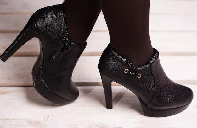 Herfst zwarte vrouwelijke schoenen met hoge hakken op een witte houten vloer.