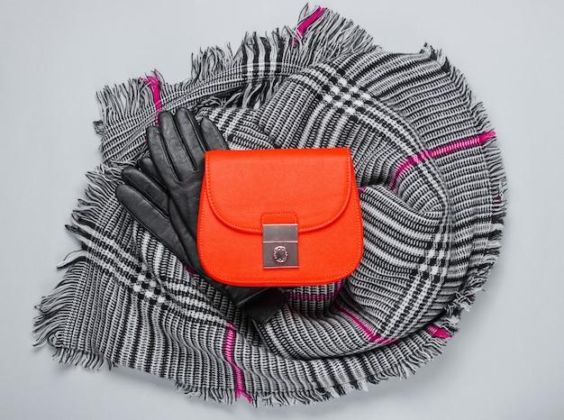 Herfstaccessoires voor dames. modieuze vrouwelijke sjaal, oranje tas, handschoenen op grijze achtergrond. bovenaanzicht