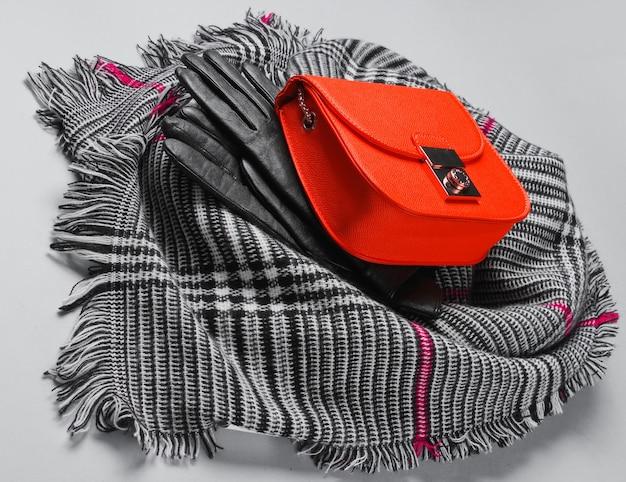 Herfstaccessoires voor dames. modieuze vrouwelijke sjaal, oranje tas, handschoenen op grijze achtergrond. zijaanzicht