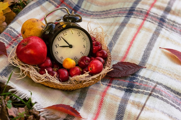 Herfstachtergrond met klokken, appels en bladeren