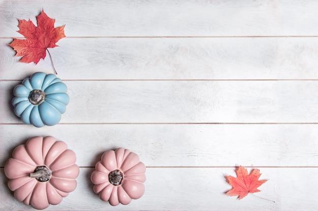 Herfstachtergrond met roze en blauwe pompoenen en bladeren in pasteltinten, bovenaanzicht met kopieerruimte