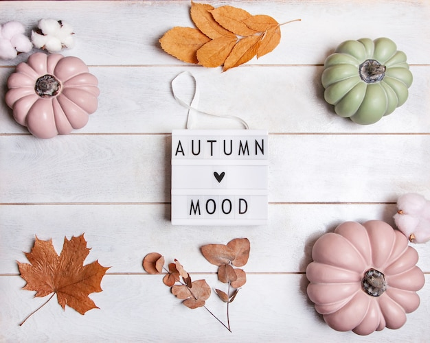 Herfstachtergrond met roze en groene pompoenen en bladeren in pasteltinten, lichtbak met de inscriptie autumn mood Premium Foto