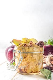 Herfstappelpecan havermout, havermoutpap met rode appels, pecannoten en karamelsaus, witte houten achtergrondkopieerruimte