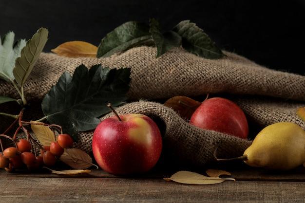 Herfstarrangement met fruitappels en -peren en gele herfstbladeren op een bruine houten tafel