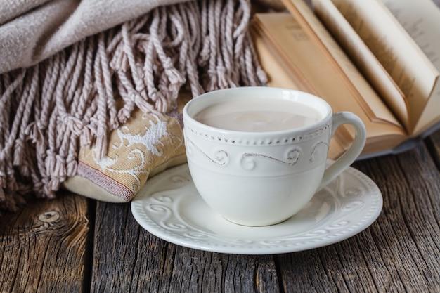 Herfstavond met warm plaid <boek en hete thee met melk