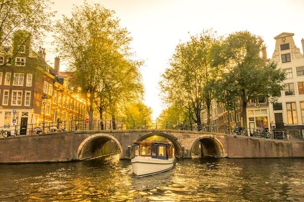 Herfstavond op de amsterdamse gracht. de boot komt onder de brug vandaan. typische huizen en veel fietsen aan het water