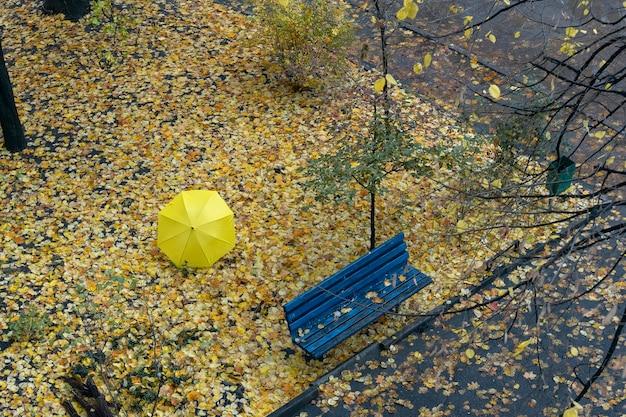 Herfstbinnenplaats met lege bank, gevallen bladeren en een voorbijganger onder een grote gele paraplu. bovenaanzicht