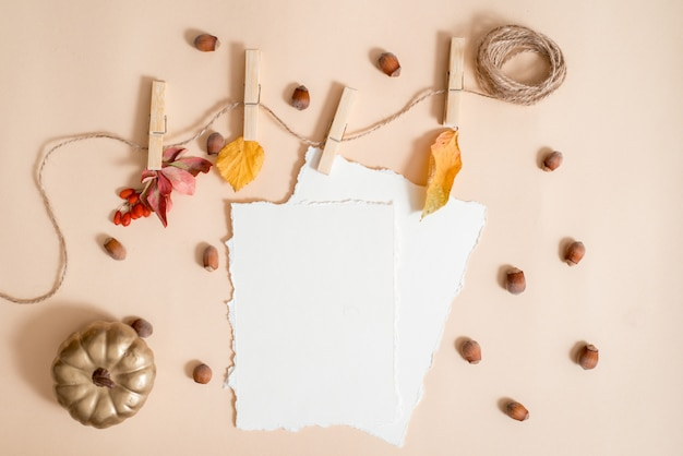 Herfstblad samenstelling, notebook. droge heldere bladeren, noten. gebreide gele warme sjaal, gouden pompoen. de t van gezellige herfst. wenskaart. trend gescheurd papier. plat lag, bovenaanzicht. copyspace.