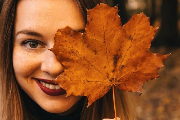 Herfstblad van het meisje sluit haar ogen en glimlacht