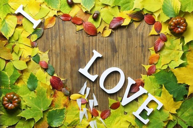 Herfstbladeren achtergrond in de vorm van een hart op houten tafel