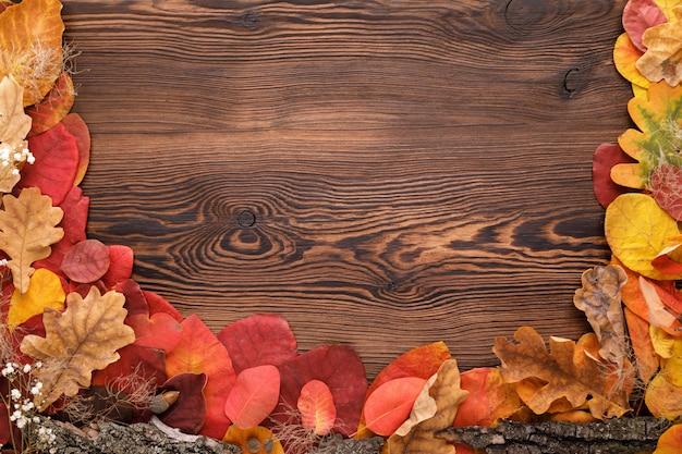 Herfstbladeren, eikels en bloemen op hout