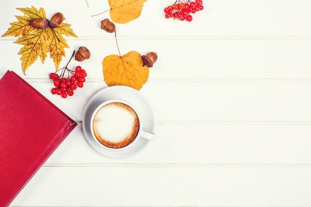 Herfstbladeren en boek op houten tafel. kop warme cappuccino voor de perfecte ochtendtijd. gezellig herfst- of wintervakantieconcept. tijd om boeken te lezen. herfst achtergrond met kopie ruimte.