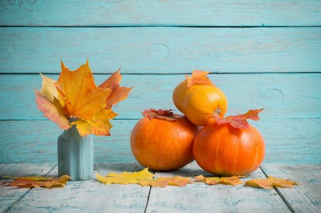 Herfstbladeren en pompoenen op blauwe houten tafel