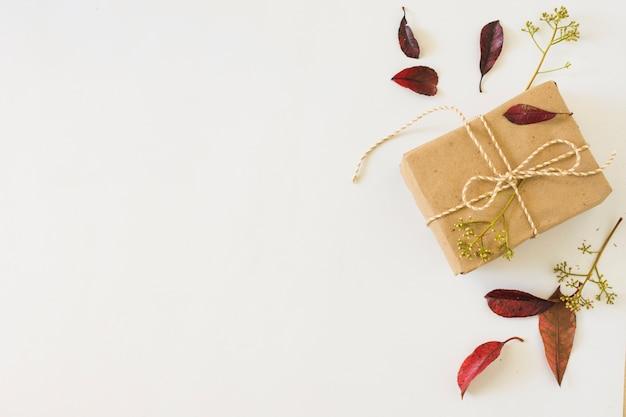 Herfstbladeren in de buurt van geschenk