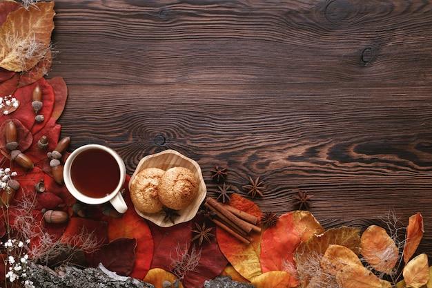 Herfstbladeren, koekjes en thee op hout