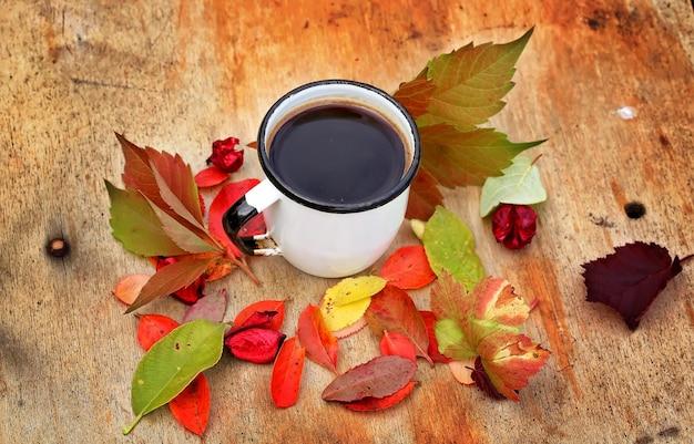 Herfstbladeren koffiemok vallen houten achtergrond