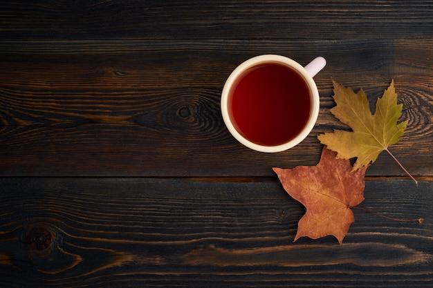 Herfstbladeren, kopje thee, een donkere houten tafel. gezellig herfststilleven