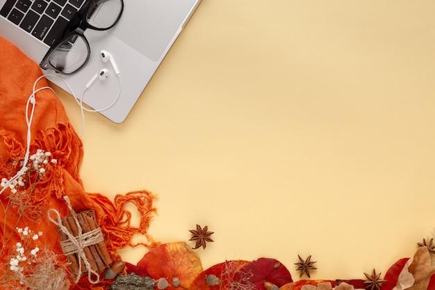 Herfstbladeren, laptop en koptelefoon op geel