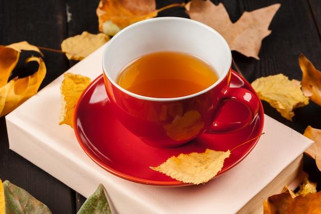 Herfstbladeren met boek en kopje thee