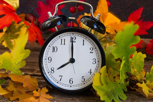 Herfstbladeren met wekker op tafel
