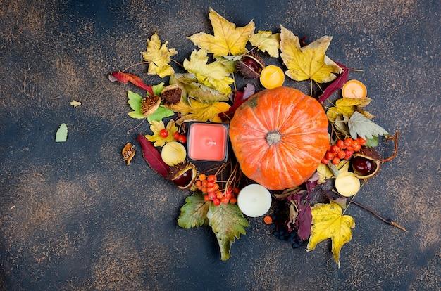 Herfstbladeren, pompoen, kastanjes, kaarsen op een donkere achtergrond