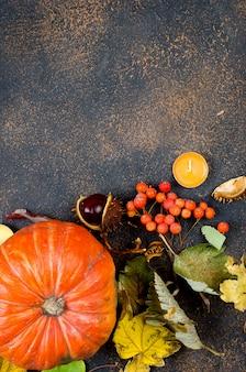 Herfstbladeren, pompoen, kastanjes, kaarsen op een donkere