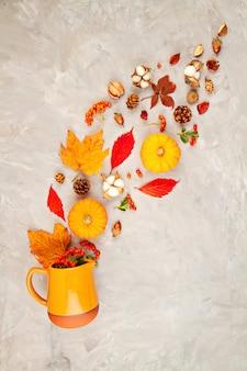 Herfstbladeren, pompoenen, bessen gieten uit een kruik