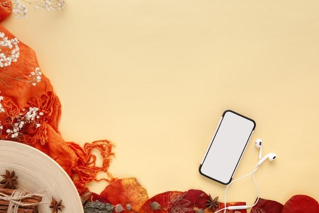Herfstbladeren, smartphone en koptelefoon op geel