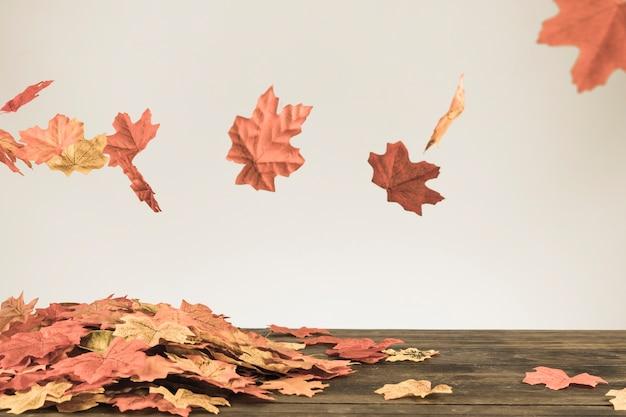 Herfstbladeren vliegen onder een bosje gebladerte