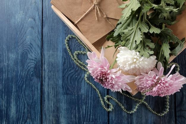 Herfstbloemen van chrysanthemum met kralen en letters op een donkerblauwe tafel met een plaats voor inscriptie.