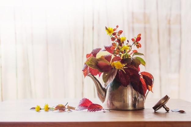Herfstboeket in ijzeren theepot op houten tafel