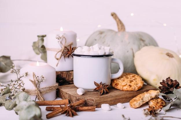 Herfstcompositie met cacao met marshmallows koekjes, pompoen en kaarsen