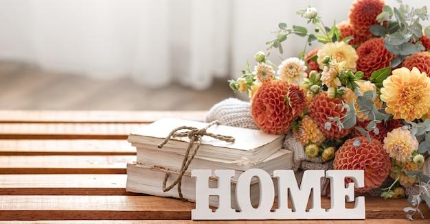 Herfstcompositie met een boeket chrysanten en decoratief woord home
