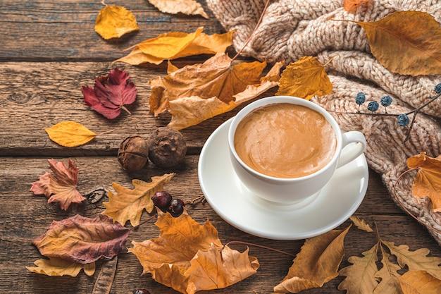 Herfstcompositie met een kopje koffie, een trui en bladeren op een bruine houten ondergrond