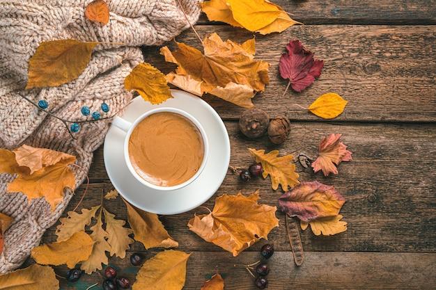 Herfstcompositie met een kopje koffie, een trui en gebladerte op een bruine achtergrond