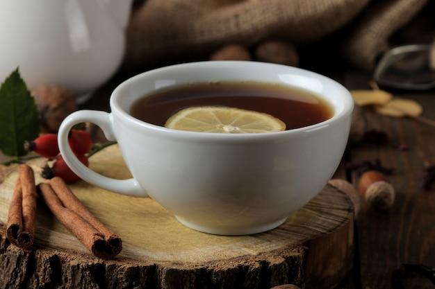 Herfstcompositie met hete thee op een houten standaard, kaneel, hondsroos, noten op een bruine houten tafel