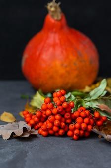 Herfstconcept met een pompoen op een donkere achtergrond met herfstbladeren die halloween vieren en